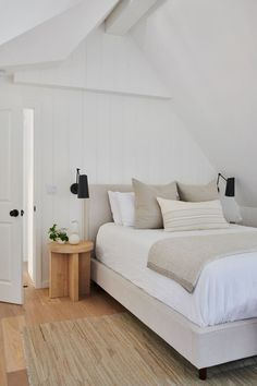 neutral bedroom design // hardwood floors // woven rug // vaulted ceiling // light gray bedding