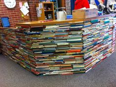 Kent took books that were being thrown out at his school library and cut both ends off with his miter saw.  He then glued them to the surface of this massive desk in his elementary school library to for a faux finish to make it look like a giant stack of books.  It took hundreds of books and a lot of noise.