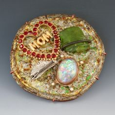 """Robert Ebendorf  'Love My Mom' Brooch in mixed media, crushed tin can, broken glass, silver, opal, and found parts. 2.75 x 2.75"""".  Artist and jeweler Robert (Bob) Ebendorf has been a leader in the art jewelry movement since the 60's."""