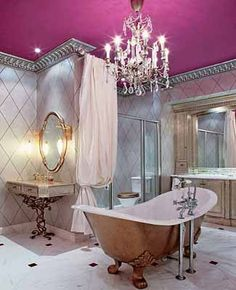 Antique bathroom decor, modern chandelier and claw foot tub, marble and wrought iron