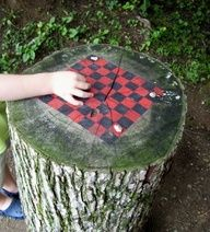 Checkers board painted on a tree stump -  this clever idea for creative outdoor play in the garden. Set up a ring of tree stump games painted with tic-tac-toe, snakes  ladders and chess for playgrounds and backyards. Use pebbles and materials from nature as game pieces  tie in a netted onion bag on a hook drilled into the tree stump. | The Micro Gardener