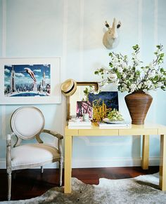 A yellow Parsons table and a French-style armchair paired with a hide rug and faux Rhino head. http://www.lonny.com/photos/Faux+Animal+Head