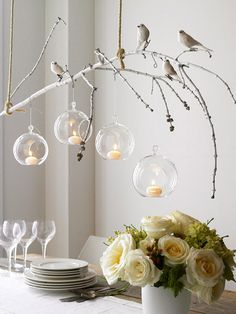 diy chandelier made of spray-painted branch, songbirds and hanging votives.