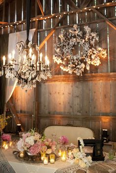 love this touch for a barn wedding_ baby's breath on grapevine wreaths--like the chandelier too