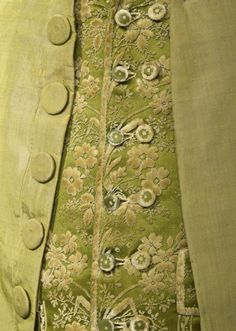Detail front view, coat and waistcoat, France, c. 1790. Green silk taffeta; waistcoat: green silk velvet with floral motifs.