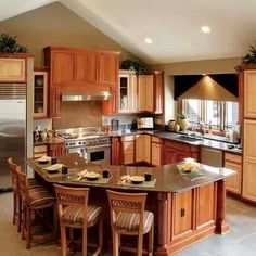 The kitchen island and the cabinets create a positive space in this kitchen. Warm colors of the room and the wood cabinets make the room pleasant and positive. The diagonal lines on the ceiling represent movement and create a nice flow to the space.