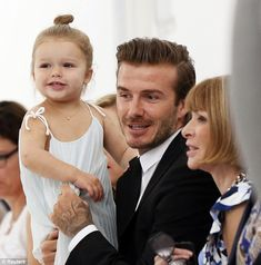 Mummy's lucky mascot! Harper Beckham sits on David's lap front row at Victoria's New York Fashion Week show