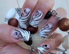 Silver, white, and black striped nail art with hearts