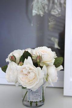 White roses in jam jar.