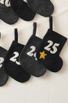 Handmade felt stockings for Advent. Made in the USA, 25 black & grey stockings with a gold star on the 25th will bring joy to each day as you