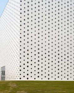 Around 6000 holes puncture the concrete exterior of this library in Kanazawa, Japan, by Kazumi Kudo and Hiroshi Horiba of Japanese firm Coelacanth K Architects.