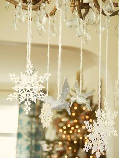 Love the glittered birds and plastic snowflakes are suspended by fuzzy white yarn from the chandelier. Silver & White Decorating Ideas --> http://www.hgtv.com/entertaining/classic-silver-and-white-christmas-table-decor/pictures/page-4.html?soc=pinterest