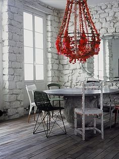 So stylish!  Paola Navone - mismatched chairs and a statement fixture