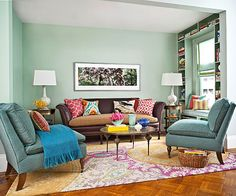 Pale green walls act as a neutral background in this colorful room: http://www.bhg.com/rooms/living-room/family/real-life-colorful-living-rooms/?socsrc=bhgpin092914inspiringarearug&page=5