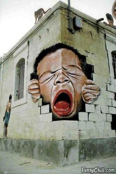 Awesome graffiti of a face coming out of the building corner... Street Art!