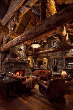 Rustic living room with stone fireplace and exposed beams in what I can only imagine is an awesome house