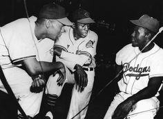 Brooklyn Dodgers infielder Jackie Robinson with Larry Doby and Satchel Paige of the Cleveland Indians.