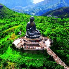 """The 85-foot-tall seated """"Giant Buddha"""" on the Ngong Ping plateau of Lantau Island serenely surveys the surrounding lush mountains and raises his right hand in blessing to the visitors who climb more than 200 steps to reach the statue's base. Photo courtesy of pindropchaos on Instagram."""