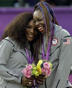 Serena Williams, left, and Venus Williams of the United States laugh together on the podium after receiving their gold medals in women's doubles at the All England Lawn Tennis Club - London 2012 Olympics
