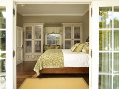 bedroom- I love the colors, the french doors, the built in armoires and window seat...