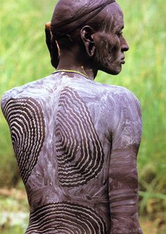 This Surma man from Ethiopia has been beautified by having himself painted with chalk to signify his readiness to marry. He will then demonstrate his valor and strength in a gigantic, ritualized, ceremonial stick fight with other young men to attract the attention of eligible young women and their families. The young Surma woman might be the one he has his eye on.