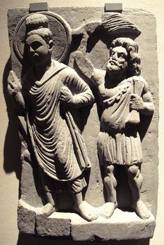 """GANDHARA The Buddha with his protector Vajrapani. Gandhara; 2nd century. Vajrapāṇi (from Sanskrit vajra, """"thunderbolt"""" or """"diamond"""" and pāṇi, lit. """"in the hand"""") is one of the earliest bodhisattvas of Mahayana Buddhism. He is the protector and guide of the Buddha, and rose to symbolize the Buddha's power."""