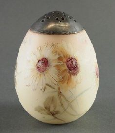 Mt Washington Burmese glass sugar shaker. Bulbous body decorated with fine floral enameling and gilded detail, with a pewter cover. 4.25 inches high