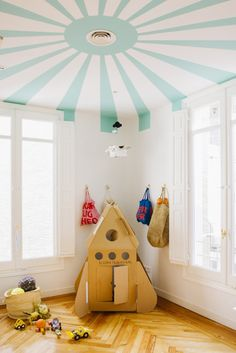 """This space rocket is one of Nicolas' favorite places. We painted the ceiling to add a little detail to the space while the white walls keep it feeling clean and light."""