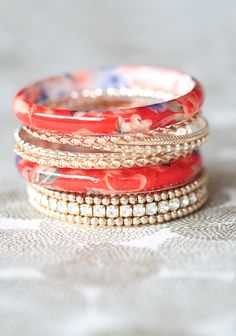 """Tropical Getaway Bangle Set 19.99 at shopruche.com. We're head over heels for this set of nine bangles in ornate styles with glittering rhinestone accents and floral resin details.2.75"""" diameter"""
