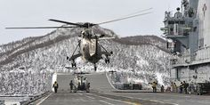 A Sea King helicopter with the Commando Helicopter Force (CHF) lifting off from the deck of HMS Illustrious.