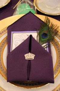 A place setting with menu, a feather detail and Mardi Gras crown accent.
