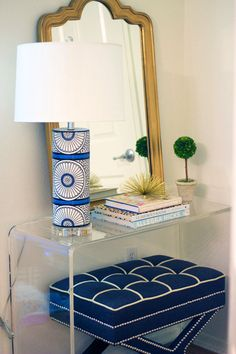 Blue and white patterned lamp, clear acrylic console table, blue and white tufted stool, and gold mirror.