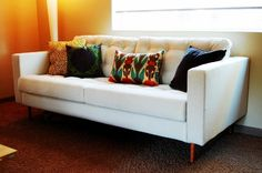 Turn a cheap ikea couch into a stylish tufted couch, add colorful pillows and voila!