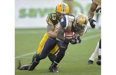 Winnipeg Blue Bombers' Demond Washington, right, is tackled by Edmonton Eskimos' Mike Miller during their CFL game in Edmonton on Friday, July 13, 2012.