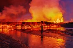 A person stands in front of the lava flow and massive smoke plumes of the Holuhraun Fissure, near the Bardarbunga Volcano, Iceland 9/02/2014