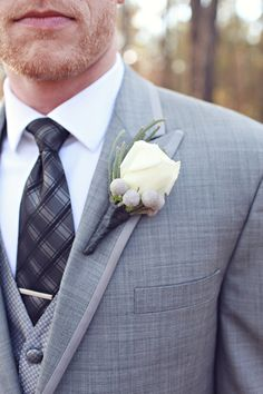 Winter boutonniere! The groom accessorized his gray suit with a wintry white rose boutonniere accented with silver brunia berries. |   Photo by J. Woodbery Photography,  Groom's Attire by Calvin Klein from Men's Wearhouse, Ceremony Floral Design by Continental Florist