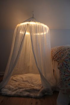 "This is so stunning and easy to make using a hula hoop for the frame and rope lighting to create a ""halo effect."" A perfect canopy! night light, reading corners, play tents, christmas lights, reading nooks, bed canopies, play area, reading areas, kid"