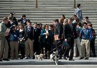 Sen. Scott Brown, R-Mass., walks his dogs across the East Plaza after posing for a group photo on the Senate steps on Wednesday, March 7, 2012. (Photo By Bill Clark/CQ Roll Call)