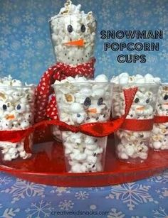 Clear plastic cups + sharpie + felt noses and scarves = snowman popcorn treat cups...cute for a party or school snack.  Could also package them in cello bags.