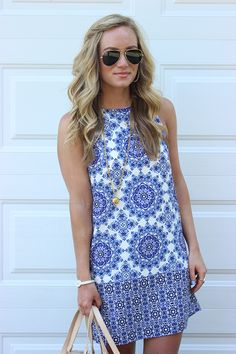 Sleeveless shift dress with colors and patterns and long gold necklace