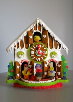 gingerbread house ideas: gingerbread cuckoo clock, gumdrop trees and gummy wreaths, and the gingerbread cookie clock face with candy cane arms