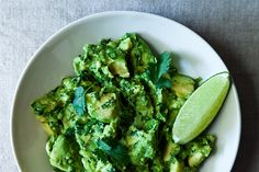 2 tablespoons finely chopped white onion  1 tablespoon minced fresh serrano or jalapeño chile, including seeds, or more to taste  1/2 teaspoon kosher salt, or 1/4 teaspoon fine salt  1/4 cup chopped cilantro, divided  1 large of 2 small ripe Mexican Hass avocados, halved and pitted  A squeeze of lime, if desired