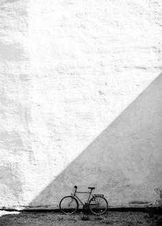 Bicycle in the shade by Smia! #nordicdesigncollective #smia #bike #shadow #shade #sun #sunshine #bicycle #photo #photography #photographer #blackandwhite #triangle #geometrical #cykel #skugga #cykeliskuggan #wall #poster #print