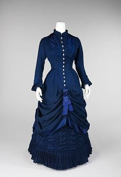 "Dress: 1881, American, wool/linen/silk/mother-of-pearl. ""The bustle silhouette, although primarily associated with the second half of the 19th century, originated in earlier fashions as a simple bump at the back of the dress, such as with late 17th-early 18th century mantuas and late 18th- early 19th century Empire dresses. The full-blown bustle silhouette had its first Victorian appearance in the late 1860s, which started as fullness in skirts moving to the back of the dress. This fullness was drawn up in ties for walking that created a fashionable puff. This trendsetting puff expanded and was then built up with supports from a variety of different things such as horsehair, metal hoops and down. Styles of this period were often taken from historical inspiration and covered in various types of trim and lace. Accessories were petite and allowed for the focus on the large elaborate gowns. Around 1874, the style altered and the skirts began to hug the thighs in the front while the bustle at the back was reduced to a natural flow from the waist to the train. This period was marked by darker colors, asymmetrical drapery, oversize accessories and elongated forms created by full-length coats. Near the beginning of the 1880s the trends altered once again to include the bustle, this time it would reach its maximum potential with some skirts having the appearance of a full shelf at the back. The dense textiles preferred were covered in trimming, beadwork, puffs and bows to visually elevate them further. The feminine silhouette continued like this through 1889 before the skirts began to reduce and make way for the S-curve silhouette."""