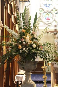 "Inside this majestic Church we arranged two huge ""Secret Garden"" style pedestal designs, both were illuminated by candle lit hurricane lamps"