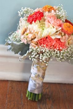 Sherbet colored bouquet, that's also budget friendly with baby's breath, peach stock, pink carnations, home grown zinnias, and dusty miller.