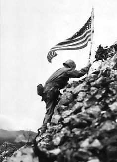 Braving Japanese sniper fire, Lt. Col. Richard P. Ross, Jr., commander of 1st Battalion, 1st Marines, places on American flag on a parapet of Shuri castle on May 29, 1945. The castle is a former enemy stronghold in southern Okinawa in the Ryukyu (Loochoo chain), situated 375 miles from Japan. This flag was first raised over Cape Gloucester and then Peleliu.