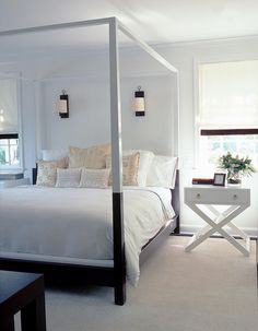Contemporary canopy bed, sconces, campaign bedside table