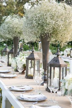 Beautiful table setting with hurricane lamps and tall vases of flowers.