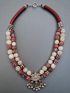 by Luda Hunter | Necklace; 2 strands of antique African skunk and eye trade beads and a centrepiece of an eight-pointed silver star pendant with dangles from Afghanistan. (The deep red skunk beads are rare wound Venetian Cornaline d'aleppo beads from the late 19th to early 20th century).  Two large knobbly Ethiopian metal beads, antique African Vulcanite heishi, Bali silver daisy spacers, bead caps and sterling silver clasp. | 370$